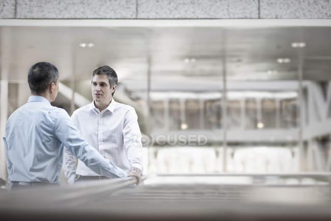 Коллеги по бизнесу стоят у ограждения — стоковое фото