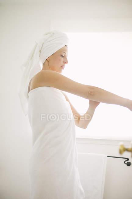 Donna in asciugamano bianco in un bagno — Foto stock