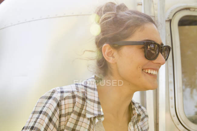 Woman wearing sunglasses by trailer — Stock Photo