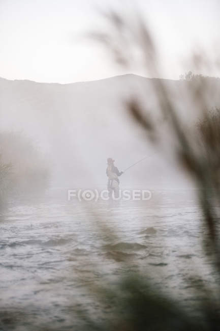 Fisherwoman flyfishing, standing in water. — Stock Photo