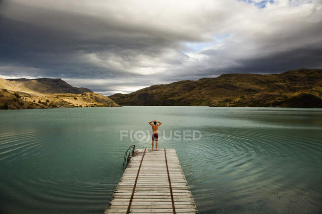 Young man at wooden pier — Stock Photo