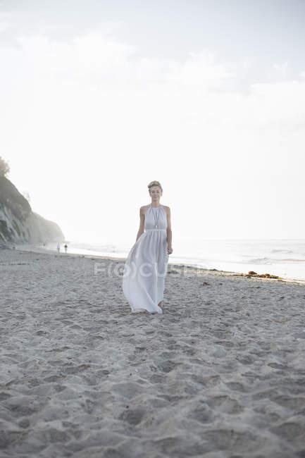 Femme debout sur une plage de sable . — Photo de stock