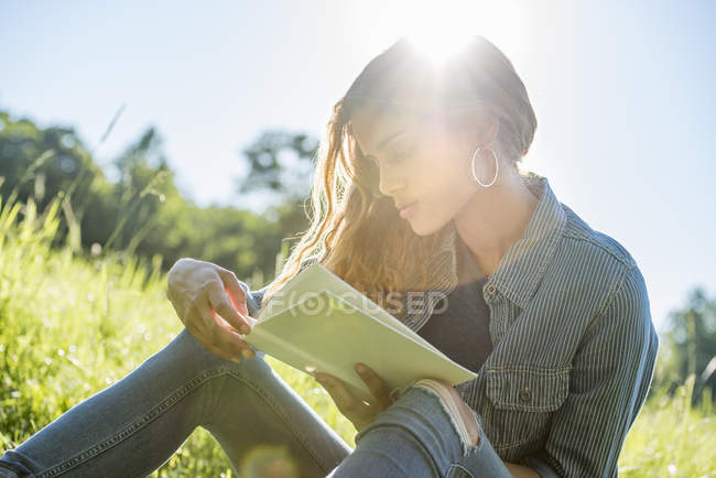 Woman  reading a book on meadow — Stock Photo