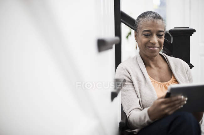 Mature woman using a digital tablet. — Stock Photo