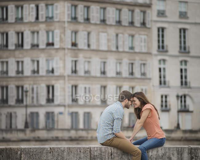 Couple sitting on the bridge over the River Seine. — Stock Photo