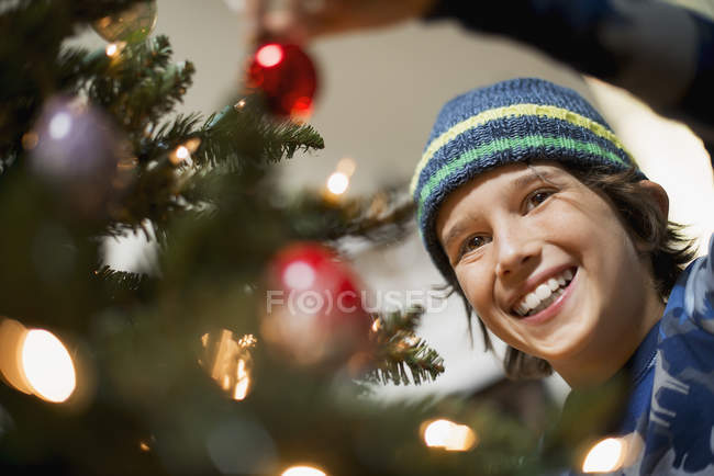 Niño colocando adornos en el árbol de Navidad - foto de stock