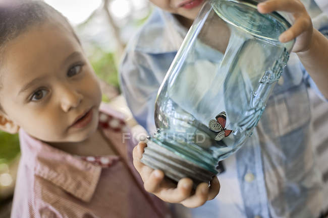 Child examining a butterfly — Stock Photo