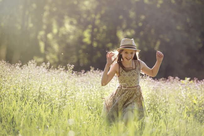 Chica caminando en un campo - foto de stock
