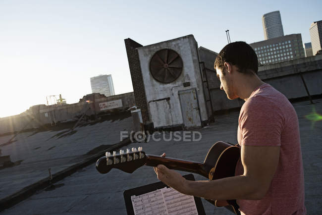 Man playing a guitar on a rooftop — Stock Photo