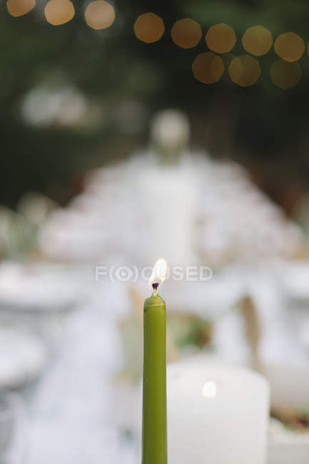Lit candle on a table set — Stock Photo