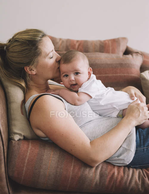 Woman lying on a sofa with baby girl. — Stock Photo