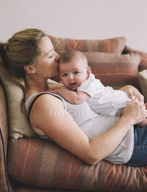 Femme allongée sur un canapé avec une petite fille. — Photo de stock