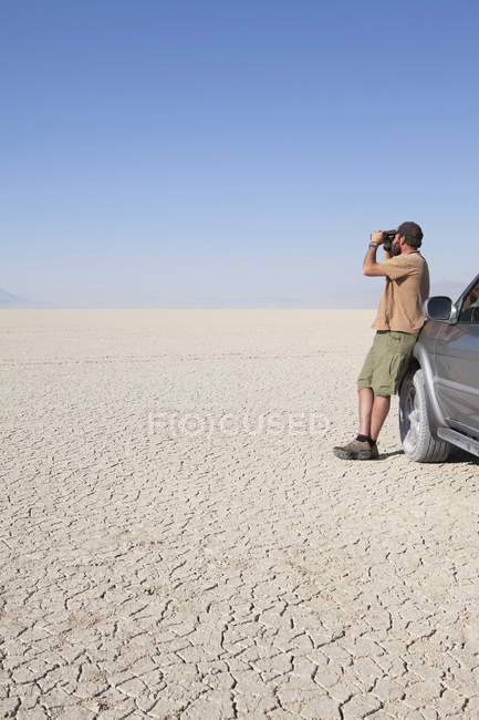 Hombre de pie en un desierto seco - foto de stock