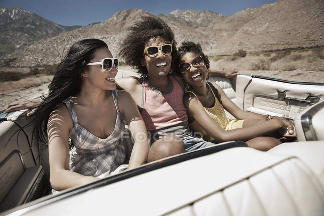 People in a pale blue convertible car — Stock Photo