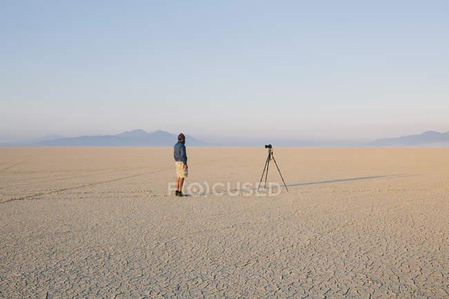 Homme à la caméra et un trépied — Photo de stock