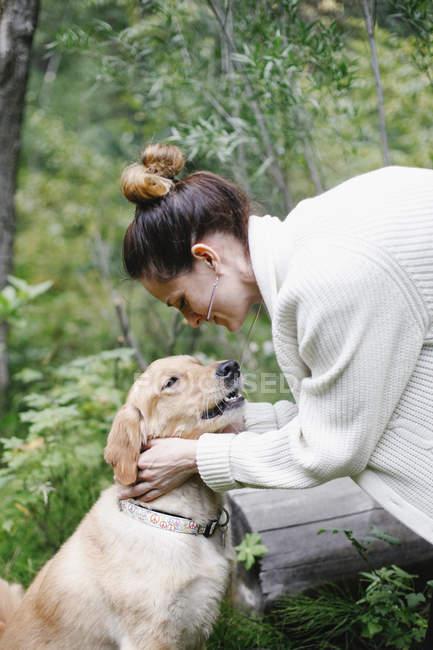 Femme caressant son chien — Photo de stock