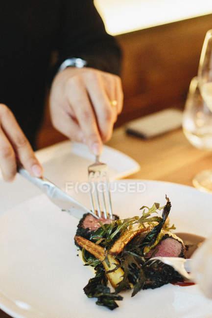 Людина, що сидить за допомогою ножем і виделкою — стокове фото