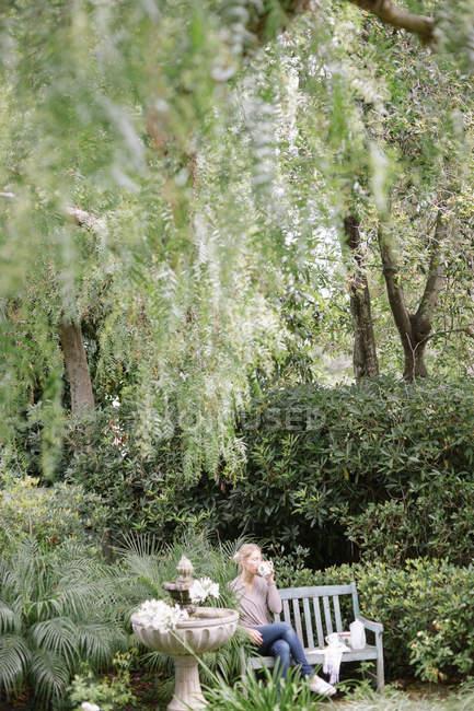 Frau sitzt auf einer Holzbank in einem Garten — Stockfoto