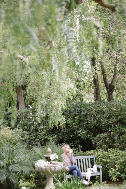Woman sitting on a wooden bench in a garden — Stock Photo