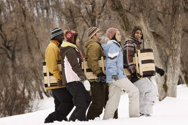 People carrying a wooden sledge — Stock Photo