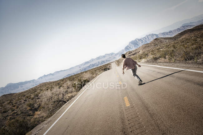 Young man riding down on skateboard. — Stock Photo