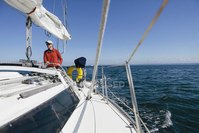 Middle aged man steering sailboat — Stock Photo