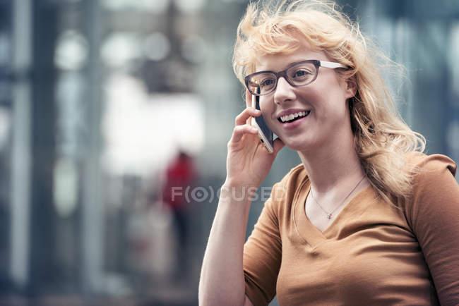 Mulher falando em um telefone celular em uma rua — Fotografia de Stock