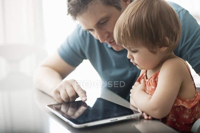 Отец и дочь смотрят на цифровой планшет — стоковое фото