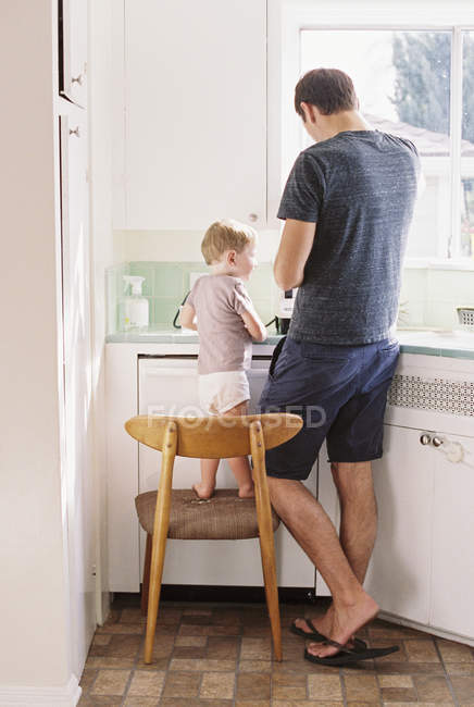 Man standing in a kitchen with son — Stock Photo