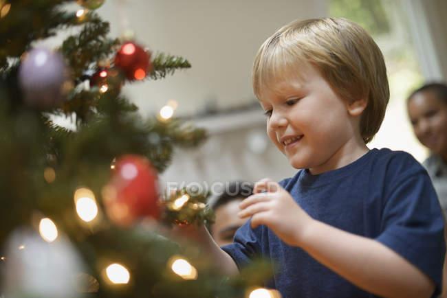 Niño colocando adornos de Navidad en árbol - foto de stock