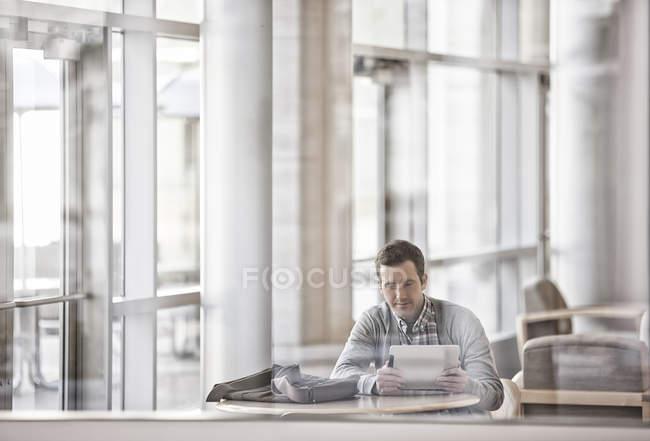 Homem sentado em officelooking no laptop — Fotografia de Stock