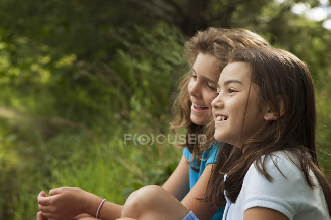 Girls sitting side by side — Stock Photo