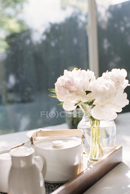 Tray with a teapot and peony flowers. — Stock Photo