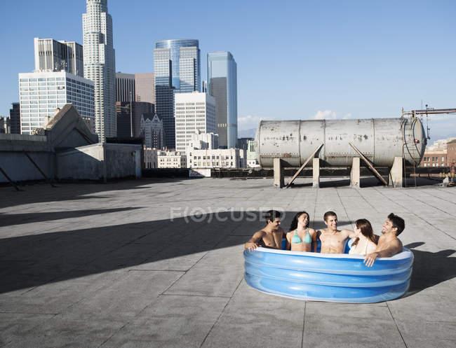 Друзья в надувном бассейне на крыше — стоковое фото
