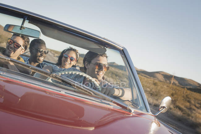 Friends in a red car on a road trip. — Stock Photo