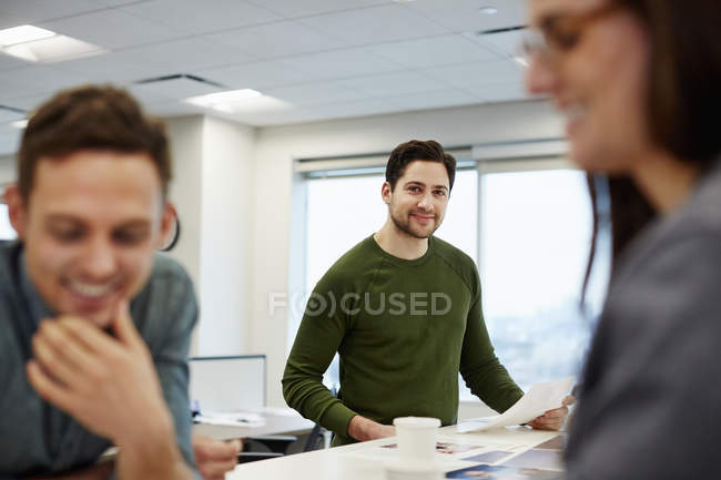 Three people in a large office — Stock Photo