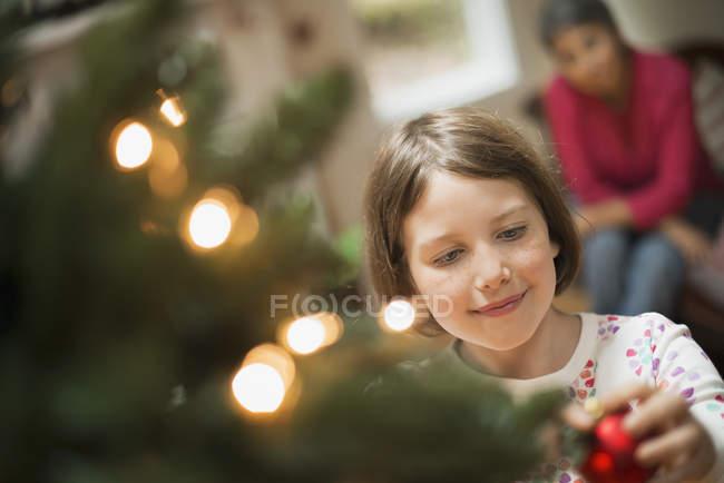 Girl poner adorno de árbol de Navidad - foto de stock