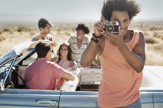 Friends by pale blue convertible — Stock Photo
