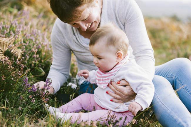 Femme assise sur le sol avec la petite fille. — Photo de stock