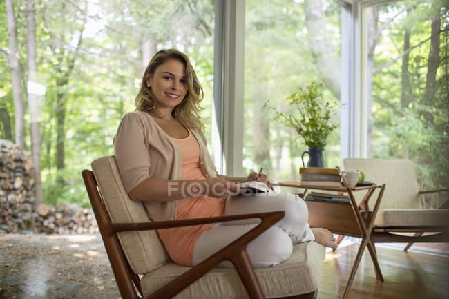 Mujer sentada sosteniendo un diario abierto - foto de stock