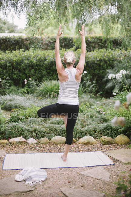 Женщина занимается йогой в саду . — стоковое фото