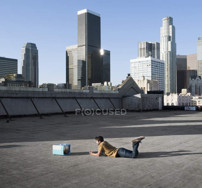 Man lying on stomach on a city rooftop — Stock Photo