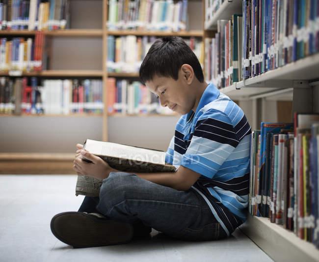Garçon dans une bibliothèque de lecture d'un livre — Photo de stock