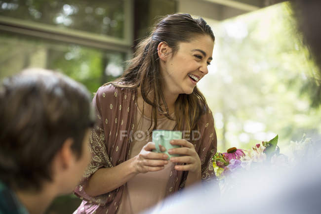 Woman at a table talking and laughing. — Stock Photo