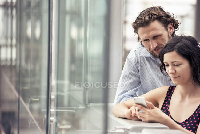 Man and woman looking at a cell phone — Stock Photo