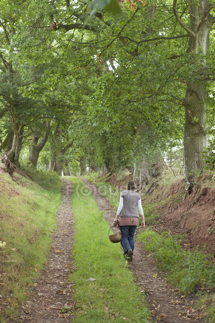 Woman walking along a country lane — Stock Photo