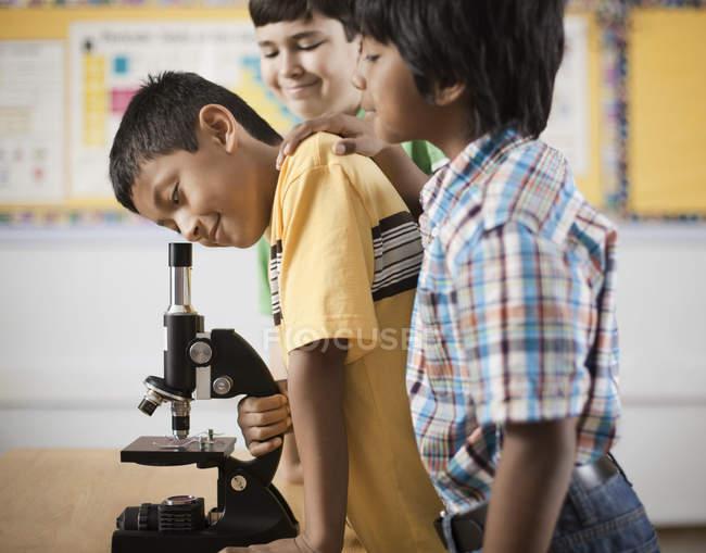 Bambini che usano un microscopio . — Foto stock