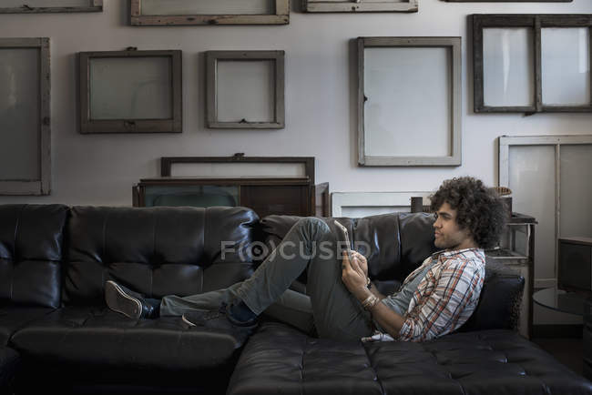 Man on a sofa using a digital tablet. — Stock Photo