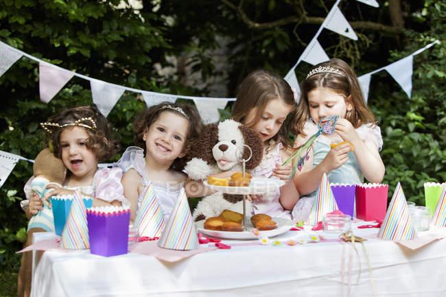 Молоді дівчата, вбравшись на вечірки в саду. — стокове фото