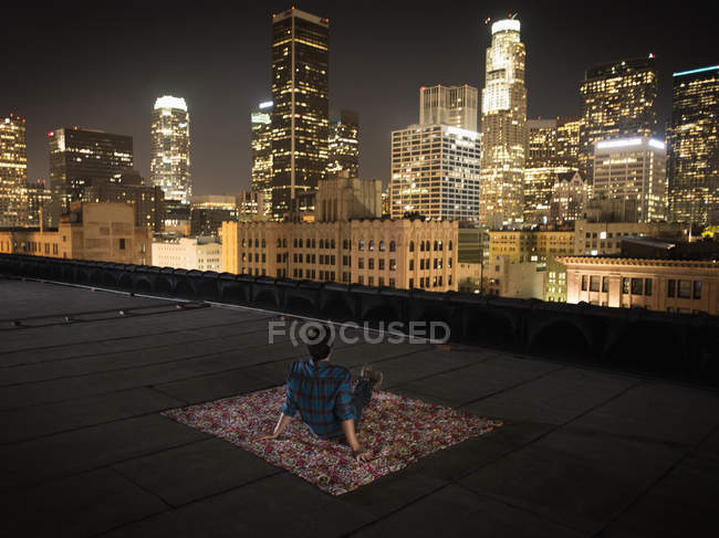 Homme assis sur un tapis sur un toit — Photo de stock
